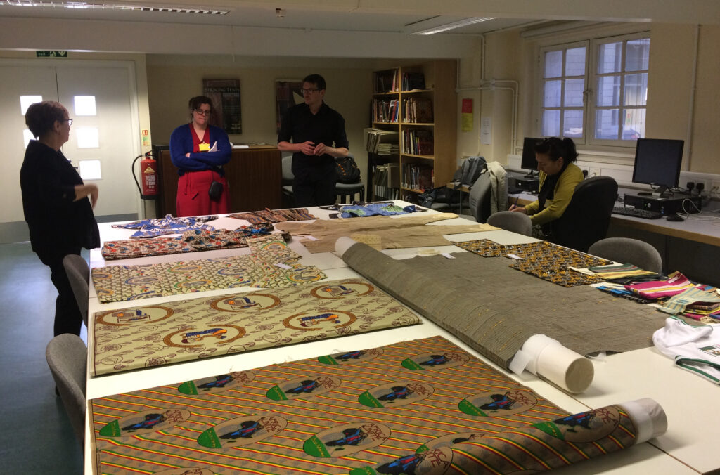Four people viewing textiles laid out on a table.