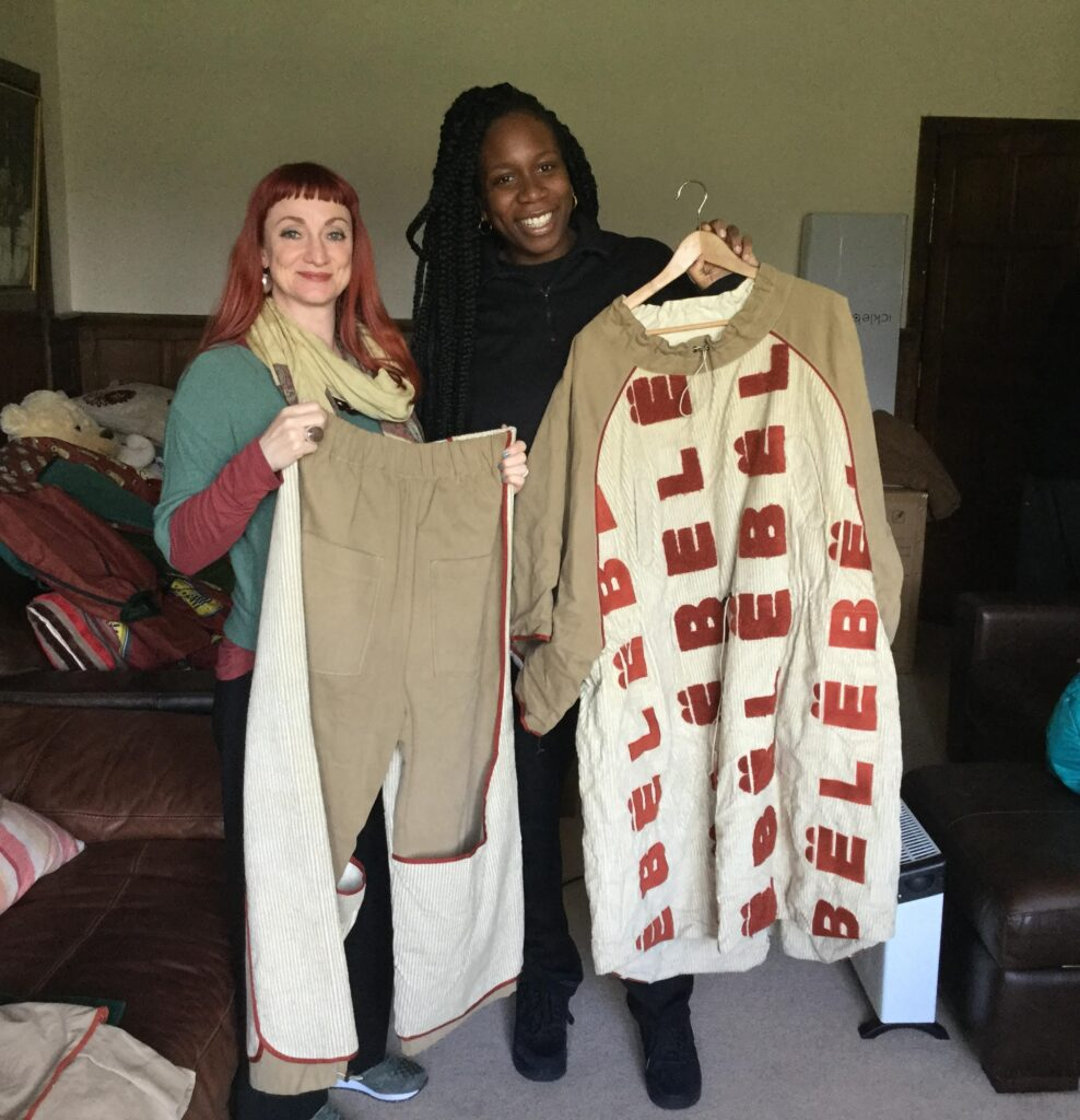 Two women holding up a pair of trousers and a shirt.