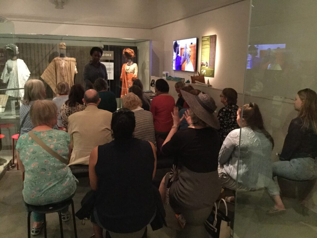 A group of people sitting in a museum gallery listening to a person talking about a display.