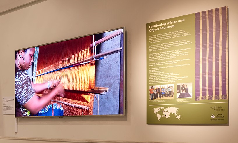 Video screen from the Aso-oke display showing a woman weaving.