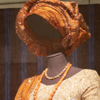 orange gele headwrap styled on mannequin