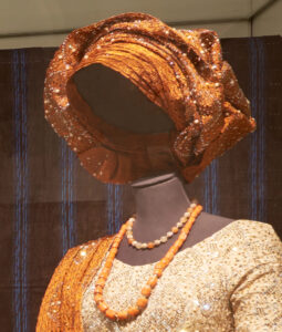 orange gele headwrap styled on mannequin