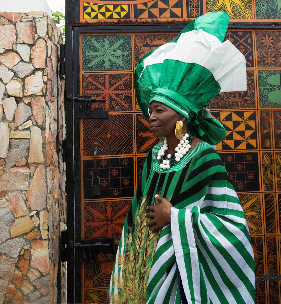 an elder woman wearing a green and white aso oke outfit