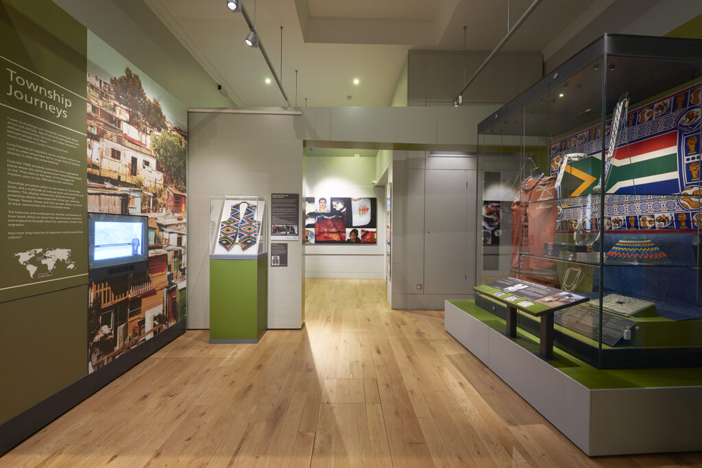 Museum gallery featuring a display of South African clothing and beadwork.
