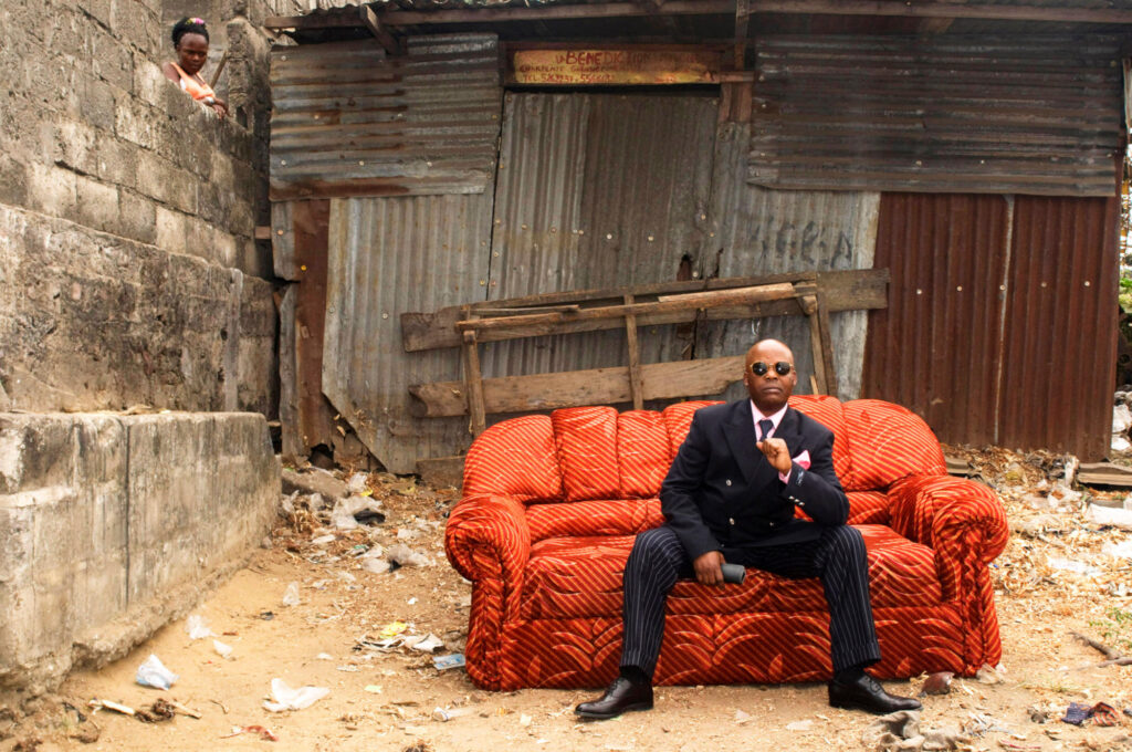 Colour photograph of a man sitting on an orange sofa, wearing a pin striped suit and dark glasses, in a yard with corrugated iron wall behind and breeze block wall to the left, and a woman in an orange top looking over the wall in the background.