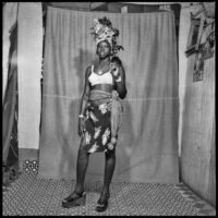 Studio portrait of a young woman wearing a white bra, wrap skirt, scarf tied around her waist, an elaborate headwrap and platform shoes.