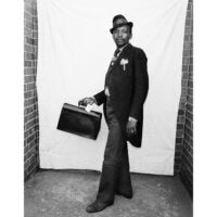 Black and white photograph of man with tailcoats and briefcase