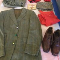 Grey check man's suit and red accessories laid out on table
