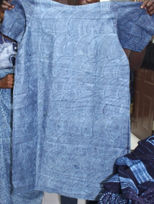 a blue tunic dyed with indigo being held up to the camera
