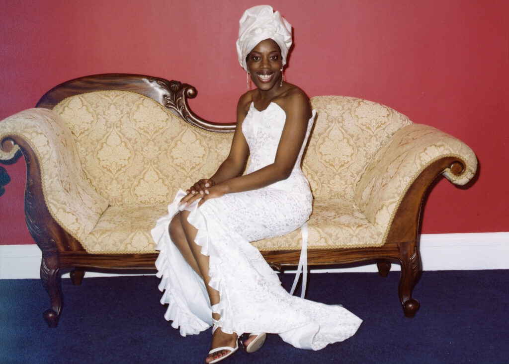 a bride wearing a white dress and headwrap, seated on a couch