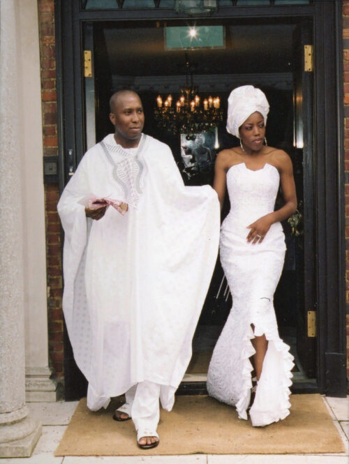 A young black couple leaving their wedding ceremony in white outfits.