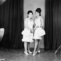 Black and white Studio portrait of two young women women wearing matching white dresses, shoes and handbags.